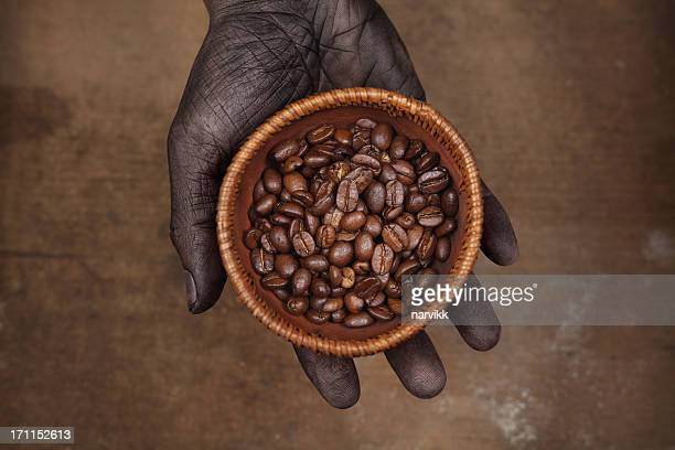 Dark Hand Holding Coffee Beans in Wooden Bowl