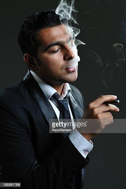 Oscuridad atractivo fumador en esmoquin