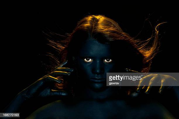 Dark painted, young woman hypnotizing with her bright eyes.