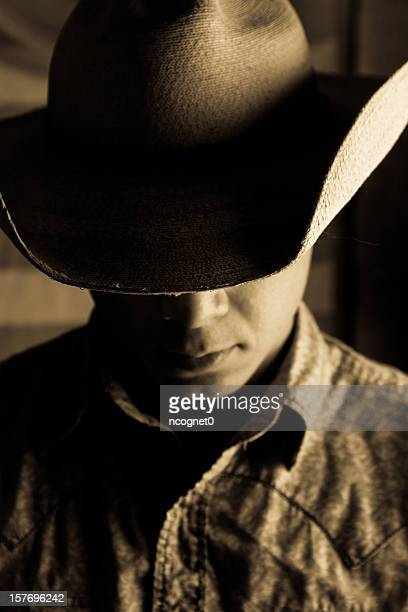 A dark portrait of a man wearing a cowboy hat