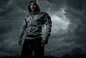Dark, dramatic portrait of a runner standing in the rain with copy space