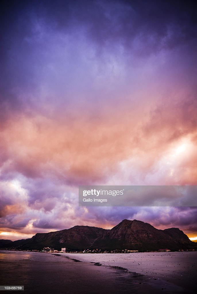 Dark purple and red clouds over mountains and beach at sunset Muizenberg Beach, Cape Peninsula, Western Cape, South Africa : Stock Photo