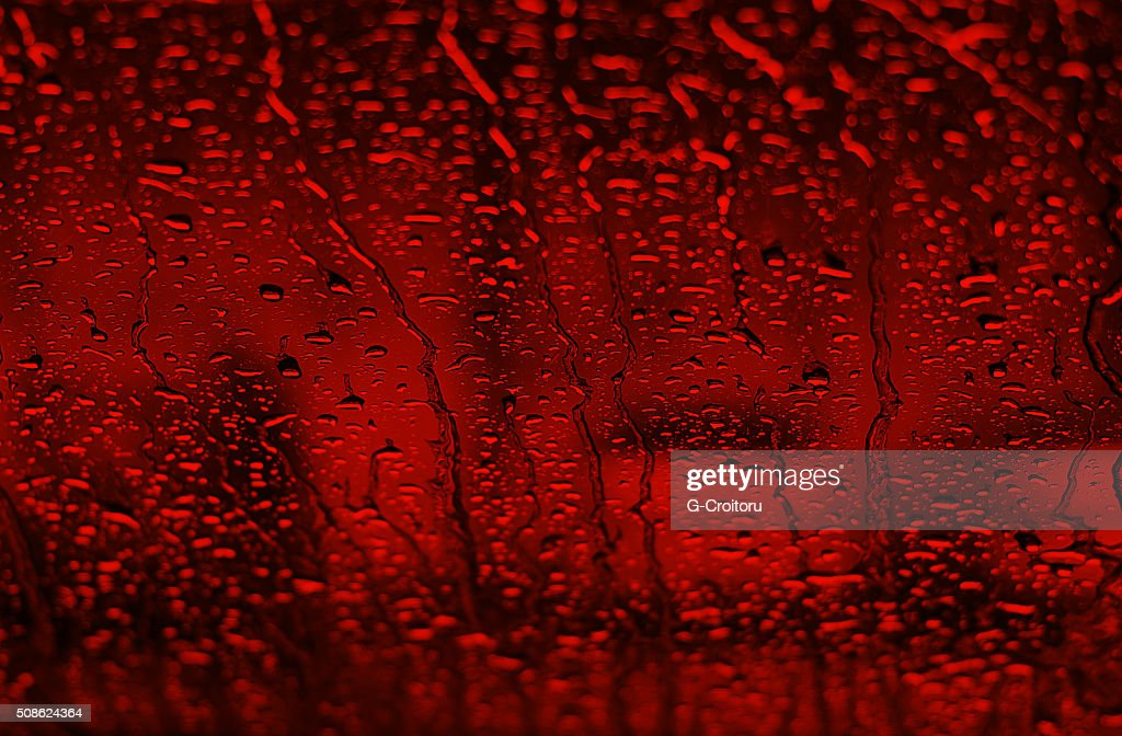 Dark red toned drops of water on the glass. : Stock Photo