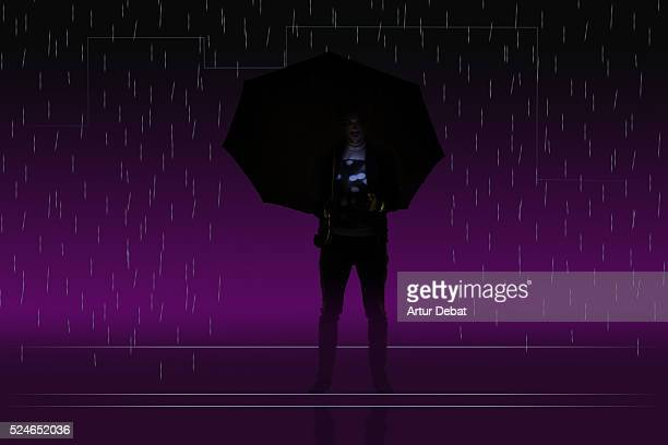 Dark silhouette of a guy isolated with a colorful background holding a smartphone under the city rain with umbrella only illuminated with the bright light of the smartphone screen.