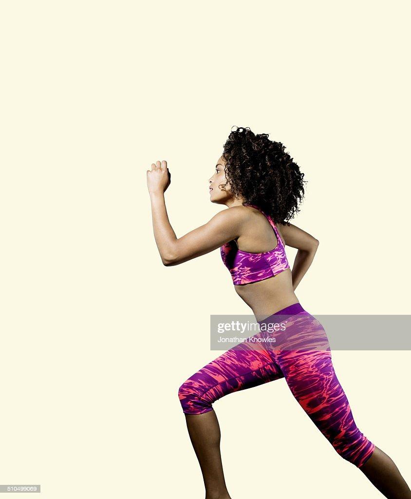 Dark skinned athletic female running, profile