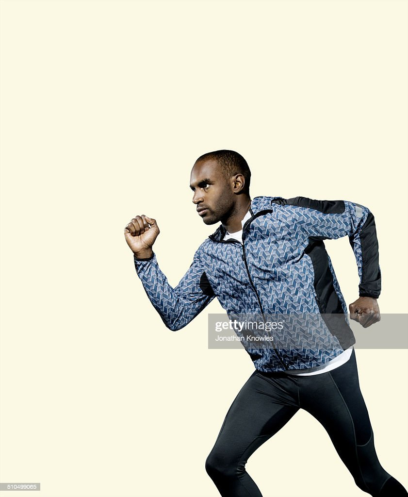 Dark skinned athletic male, running, profile