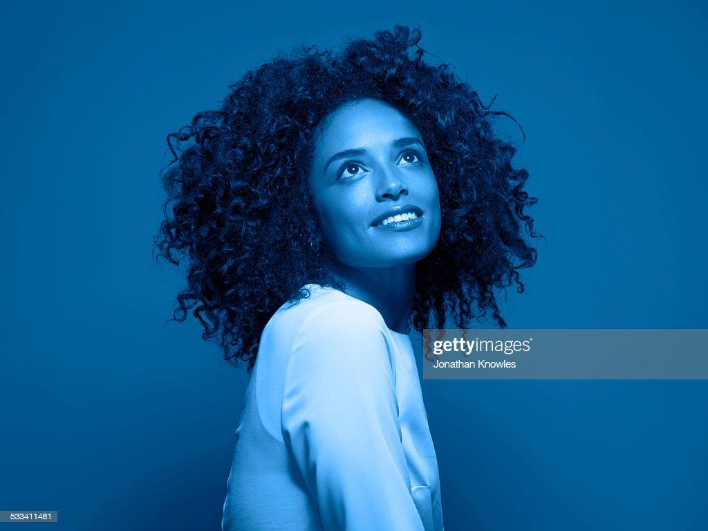 Dark skinned female looking up, smiling