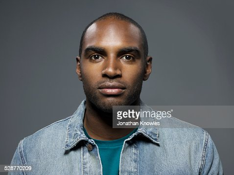 Dark skinned man looking straight into camera