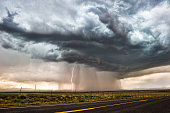 Dramatic thunderstom clouds with rain and cloud-to-ground lightning over the plains of New Mexico.
