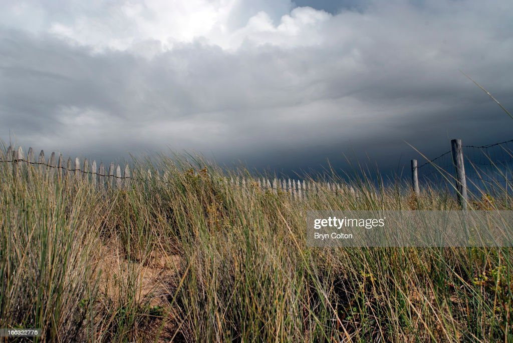 Dark storm clouds gather above green Marram grass on the sand dunes along the coastline near Saint-Jean-de-Monts, Vendee, France, on Friday, August 18, 2006.
