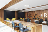 Coworking corner with dark wooden and black walls, concrete and wooden floor, tables with black and yellow chairs. 3d rendering mock up