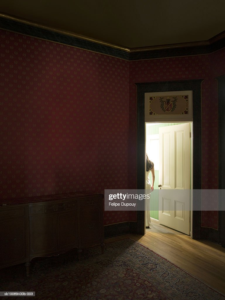 Darkened room with woman standing in doorway : Stock Photo