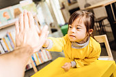 High five. Dark-eyed sunny child giving high five to her teacher in the inclusive kindergarten