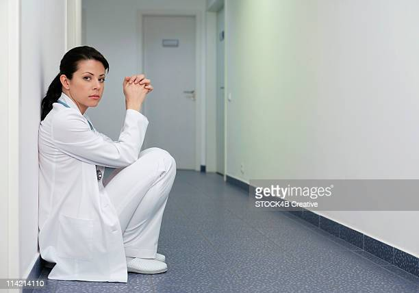 Dark-haired female doctor crouching in a hall