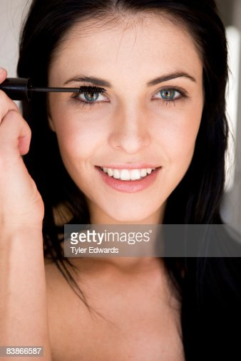 Dark-haired woman applying mascara