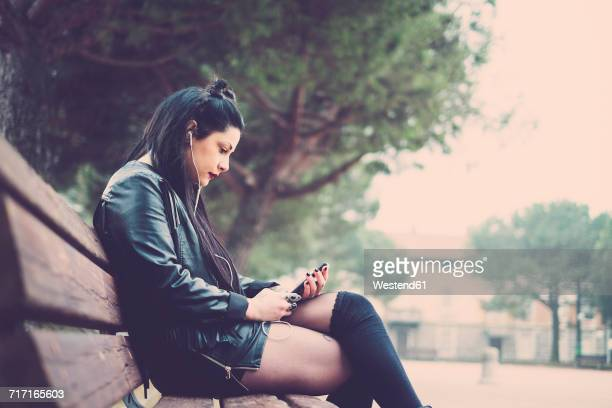 Dark-haired young woman sitting on bench listening music with earphones and smartphone