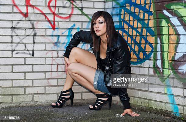Dark-haired young woman wearing hot pants, a black leather jacket and high heels posing in front of a wall with graffiti