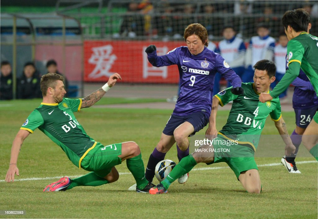 Darko Matic (L) and Zhou Ting (R) Beijing Guo'an tackle Ishihara Naoki (C) of Japanese team Sanfrecce Hiroshima during their AFC Champions League Group G football match at the Workers Stadium in Beijing on March 13, 2013. Guo'an went on to win 2-1. AFP PHOTO/ Mark RALSTON