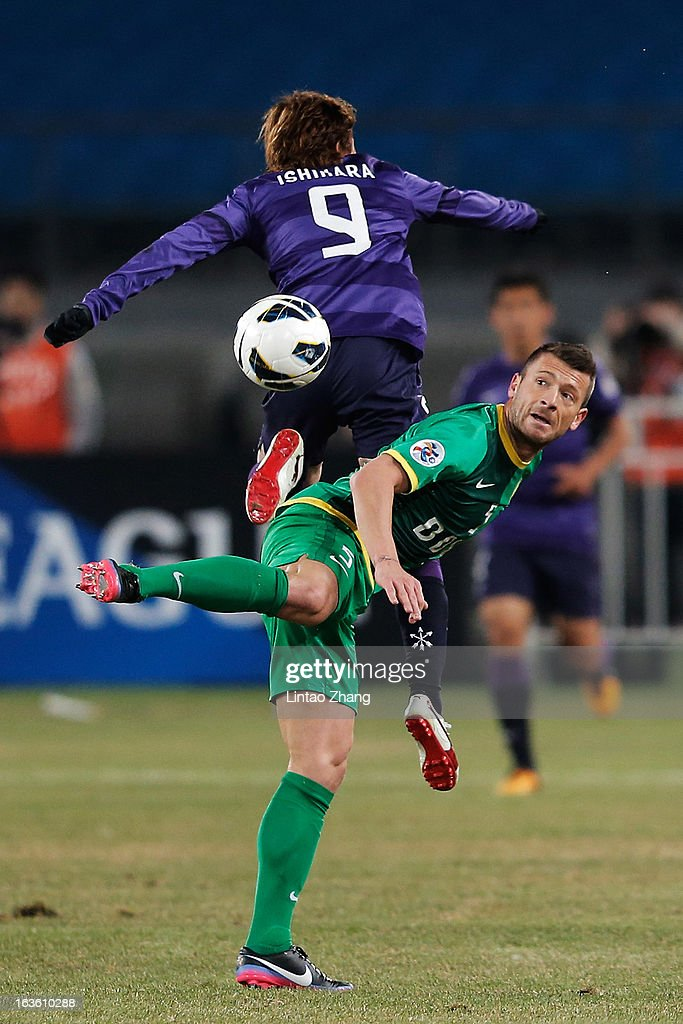 Darko Matic (R) of Beijing Guo'an competes for an aerial ball with Naoki Ishihara of Hiroshima Sanfrecce celebrates scoring his first goal during the AFC Champions League Group match between Hiroshima Sanfrecce and Beijing Guoan at Beijing Workers' Stadium on March 13, 2013 in Beijing, China.