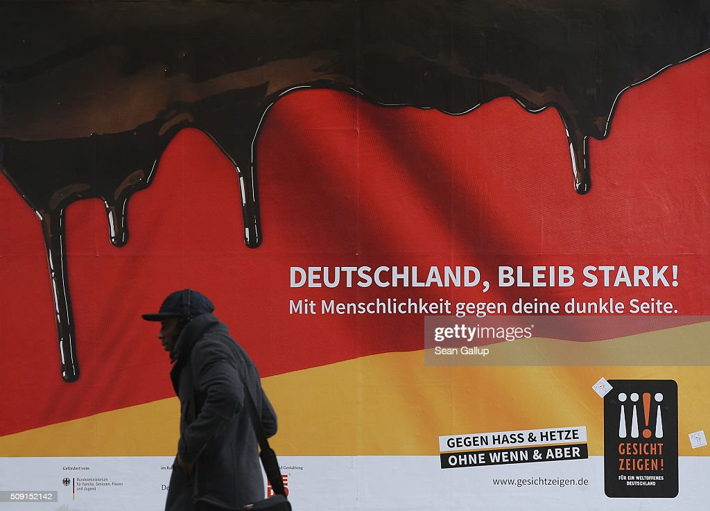 A dark-skinned man walks past a poster showing the German flag with a dripping black portion and that reads: 'Germany, stay strong! With humanity against your dark side,' and below: 'Against hate and baiting, no if and but' on February 9, 2016 in Berlin, Germany. The poster is part of a campaign supported by Germany's Ministry for Families, Seniors, Women and Youth in an effort to encourage more tolerance, particularly of the 1.1 million migrants and refugees that arrived in Germany in 2015. Though a majority of Germans have shown a strong willingness to accept the newcomers and thousands have volunteered to help them, the country has also seen a growing number of attacks, including beatings, arson, vandalism and other violence against refugees and refugee shelters.