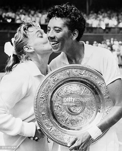 Darlene Hard kisses Althea Gibson after Gibson defeated her 63 63 in the finals of the women's singles tennis championship at Wimbledon Gibson was...