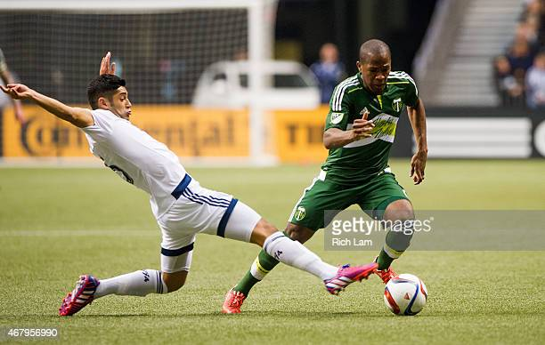 Darlington Nagbe of the Portland Timbers avoids the tackle of Matias Laba of the Vancouver Whitecaps FC in MLS action on March 2015 at BC Place...