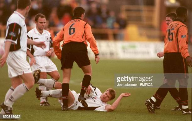 Darlington's Marco Gabbiadini feels the full force of a boot in the face from Barnet's Mark Arber