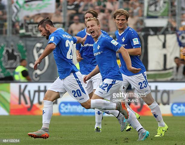 Darmstadt's midfielder Marcel Heller celebrates with teammates after scoring the 10 during the German first division Bundesliga football match SV...