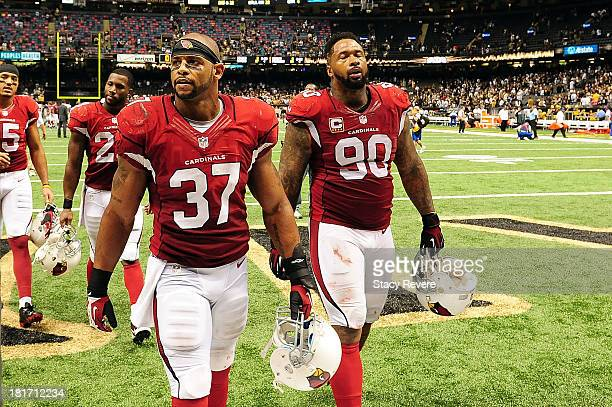 Darnell Dockett and Yeremiah Bell of the Arizona Cardinals leave the field following a game against the New Orleans Saints at the MercedesBenz...