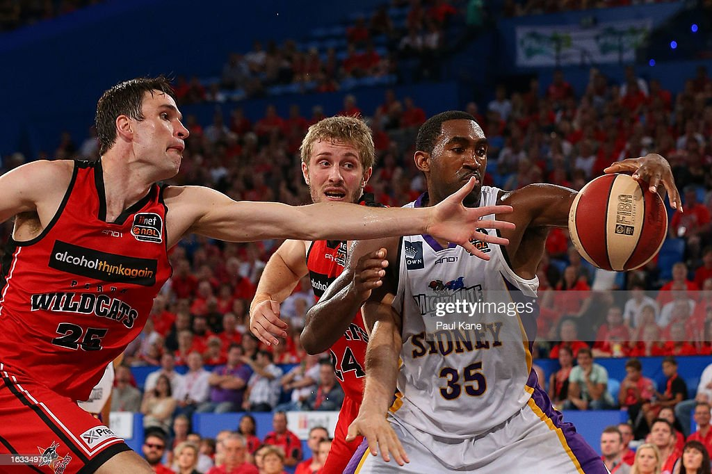 Darnell Lazare of the Kings gathers the ball against Jeremiah Trueman and Jesse Wagstaff of the Wildcats during the round 22 NBL match between the Perth Wildcats and the Sydney Kings at Perth Arena on March 8, 2013 in Perth, Australia.