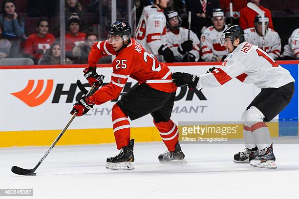 Darnell Nurse of Team Canada carries the puck away from Luca Hischier of Team Switzerland during the 2015 IIHF World Junior Hockey Championship...