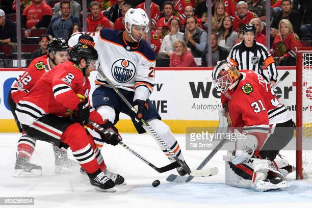 Darnell Nurse of the Edmonton Oilers and Duncan Keith of the Chicago Blackhawks work to get at the puck in front of goalie Anton Forsberg in overtime...