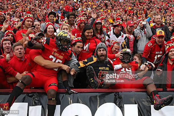 Darnell Savage Jr #26 and Cavon Walker of the Maryland Terrapins jump into the stands before playing the Wisconsin Badgers at Byrd Stadium on...