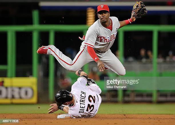 Darnell Sweeney of the Philadelphia Phillies turns a double play as Derek Dietrich of the Miami Marlins slides into second during a game at Marlins...