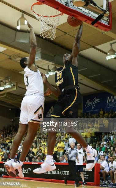 Darral Willis Jr #21 of the Wichita State Shockers attempts a dunk ahead of DJ Harvey of the Notre Dame Fighting Irish during the first half of their...