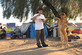 Darrel Romero plays with his dog 'Crunk' in Tent City in Ontario California The City of Ontario opened Tent City for the City's residents who were...