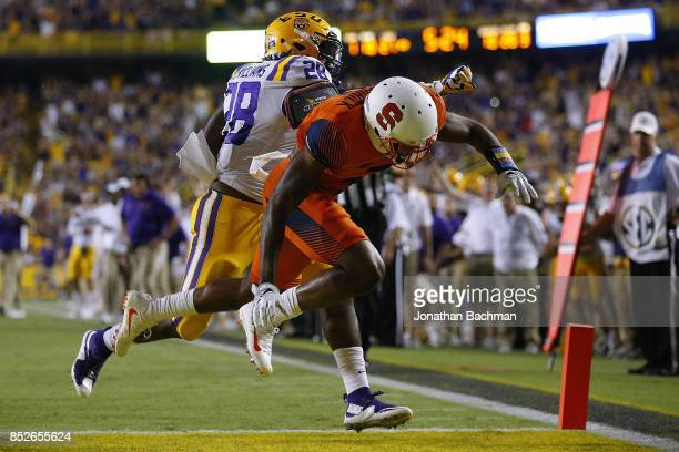 Darrel Williams of the LSU Tigers scores a touchdown as Christopher Fredrick of the Syracuse Orange defends during the second half of a game at Tiger...
