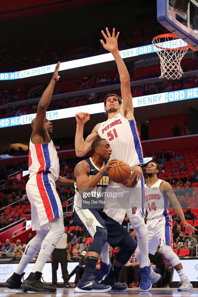 Darrell Arthur #00 of the Denver Nuggets drive to the basket against Boban Marjanovic #51 of the Detroit Pistons at Little Caesars Arena on December 12, 2017 in Detroit, Michigan.