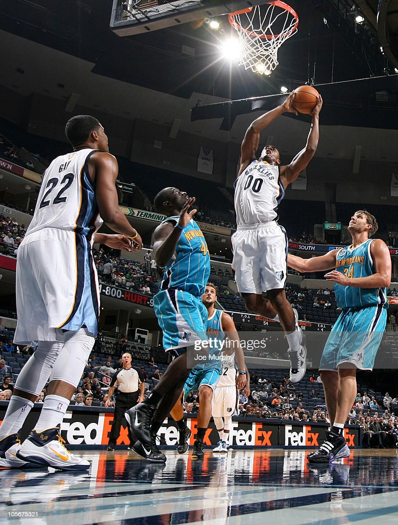 <a gi-track='captionPersonalityLinkClicked' href=/galleries/search?phrase=Darrell+Arthur&family=editorial&specificpeople=4102032 ng-click='$event.stopPropagation()'>Darrell Arthur</a> #00 of the Memphis Grizzlies dunks against Pops Mensa-Bonsu #44 and <a gi-track='captionPersonalityLinkClicked' href=/galleries/search?phrase=Aaron+Gray+-+Basketball+Player&family=editorial&specificpeople=666453 ng-click='$event.stopPropagation()'>Aaron Gray</a> #34 of the New Orleans Hornets on October 18, 2010 at the FedExForum in Memphis, Tennessee.