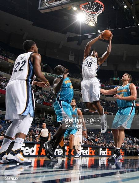 Darrell Arthur of the Memphis Grizzlies dunks against Pops MensaBonsu and Aaron Gray of the New Orleans Hornets on October 18 2010 at the FedExForum...