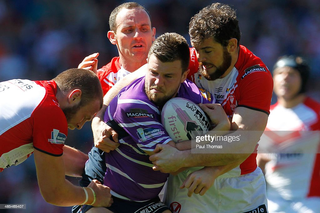 Darrell Goulding of Wigan is tackled by Josh Jones Lance Hohaia and Paul Wellens during the Super League match between St Helens and Wigan Warriors...