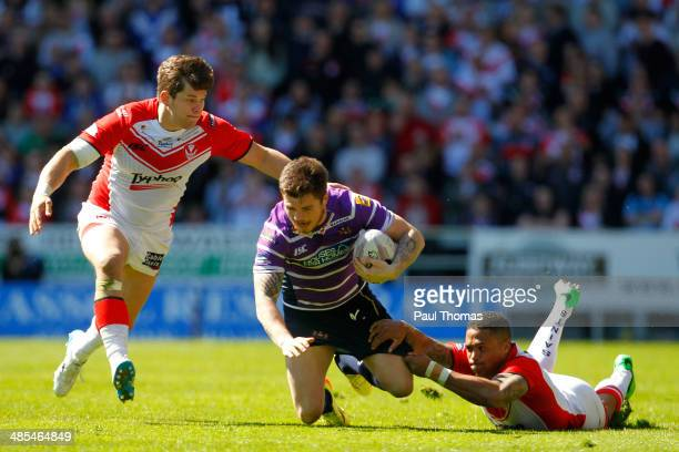 Darrell Goulding of Wigan is tackled by Louie McCarthyScarsbrook and Jordan Turner of St Helens during the Super League match between St Helens and...