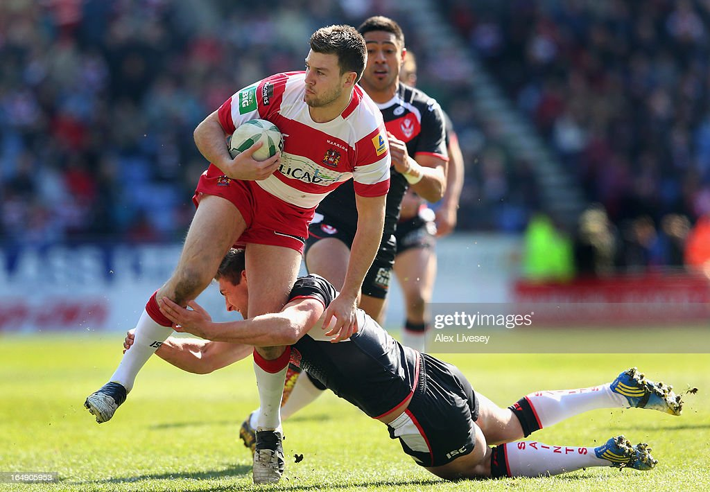 Darrell Goulding of Wigan Warriors is tackled by Tom Makinson of St Helens during the Super League match between Wigan Warriors and St Helens at DW Stadium on March 29, 2013 in Wigan, England.