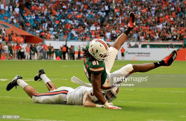Darrell Langham of the Miami Hurricanes makes a catch over Quin Blanding of the Virginia Cavaliers during a game at Hard Rock Stadium on November 18...