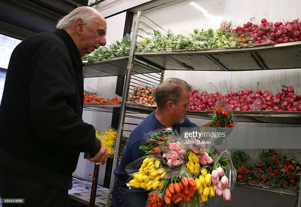 Darrell Torchio (R) helps a customer pick out flowers at the San Francisco Flower Mart on August 29, 2014 in San Francisco, California. The future of more than 100 flower businesses at the historic San Francisco Flower Mart hangs in the balance as Los Angeles based realty group Kilroy Realty Corp. is planning on purchasing the Flower Mart property. Kilroy has proposed a plan to build a tech campus on the site.