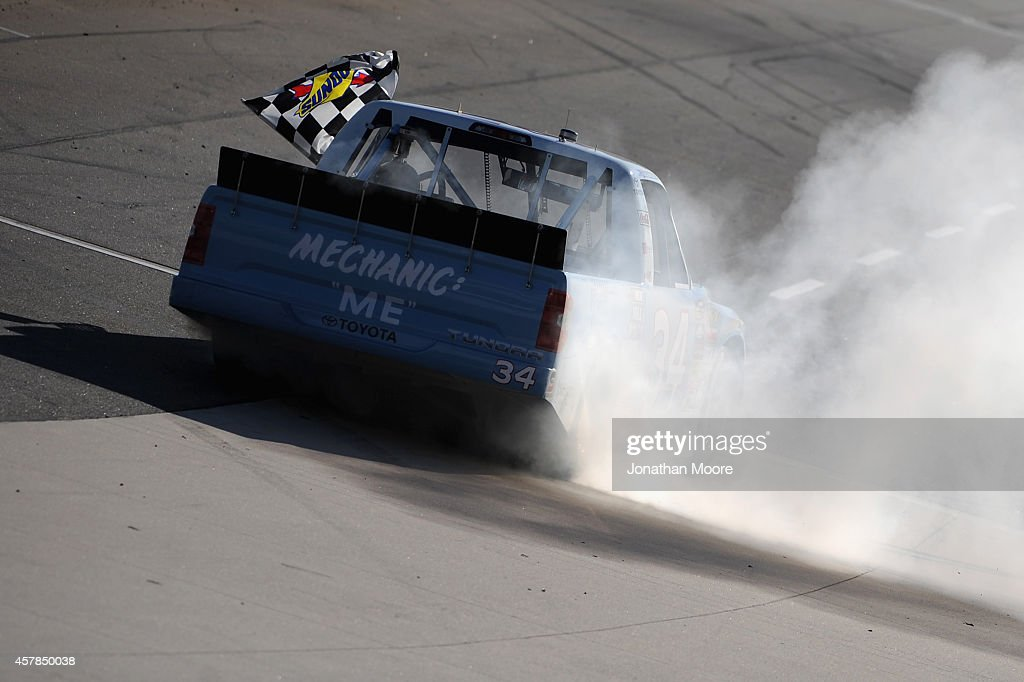 Darrell Wallace, Jr., driver of the #34 2015 NASCAR Hall of Fame Inductee Wendell Scott Toyota, celebrates with a burnout and the checkered flag after winning the NASCAR Camping World Truck Series Kroger 200 at Martinsville Speedway on October 25, 2014 in Martinsville, Virginia.