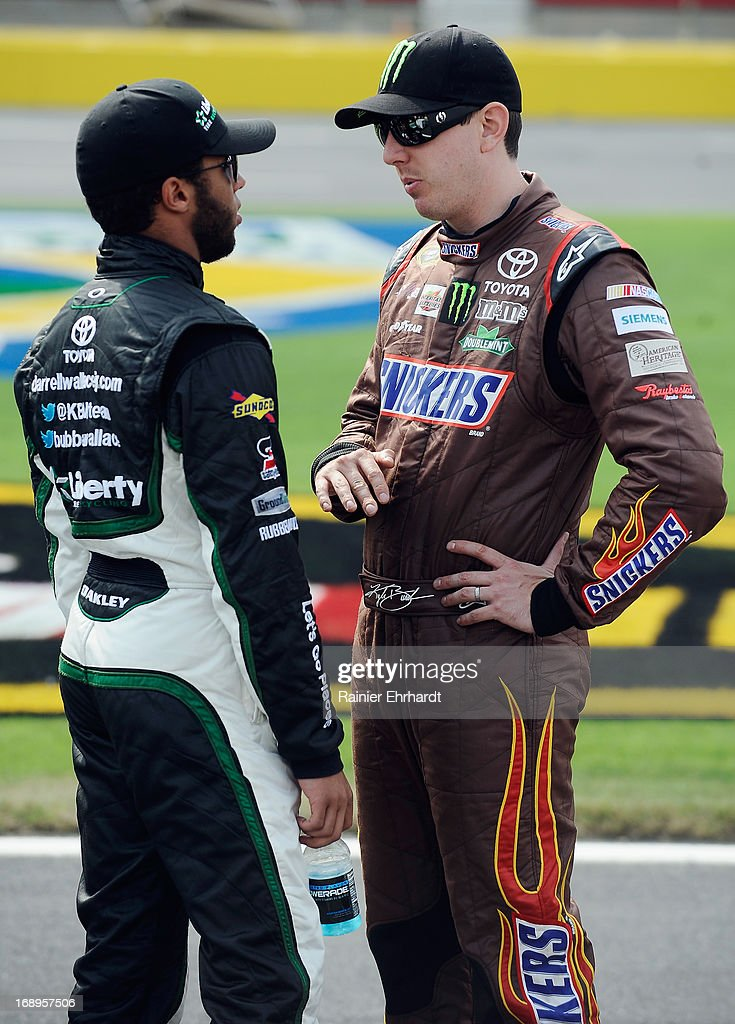 Darrell Wallace Jr., driver of the #54 Liberty Tire Recycling Toyota (L), talks with Kyle Busch, driver of the #51 Toyota Care Toyota, during qualifying for the NASCAR Camping World Truck Series North Carolina Education Lottery 200 at Charlotte Motor Speedway on May 17, 2013 in Concord, North Carolina.