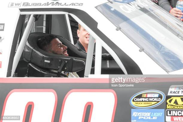 Darrell Wallace Jr driver of the Maestro's Classic Chevrolet smiles while sitting in his car in Gatorade Victory Lane after winning the Camping World...