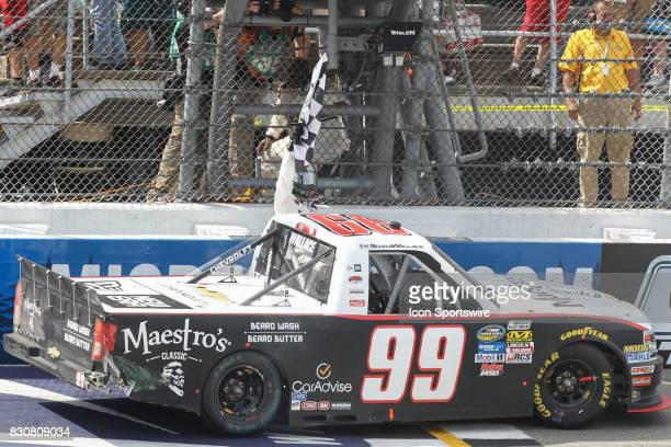 Darrell Wallace Jr driver of the Maestro's Classic Chevrolet waves the checkered flag at the finish line after winning the Camping World Truck Series...