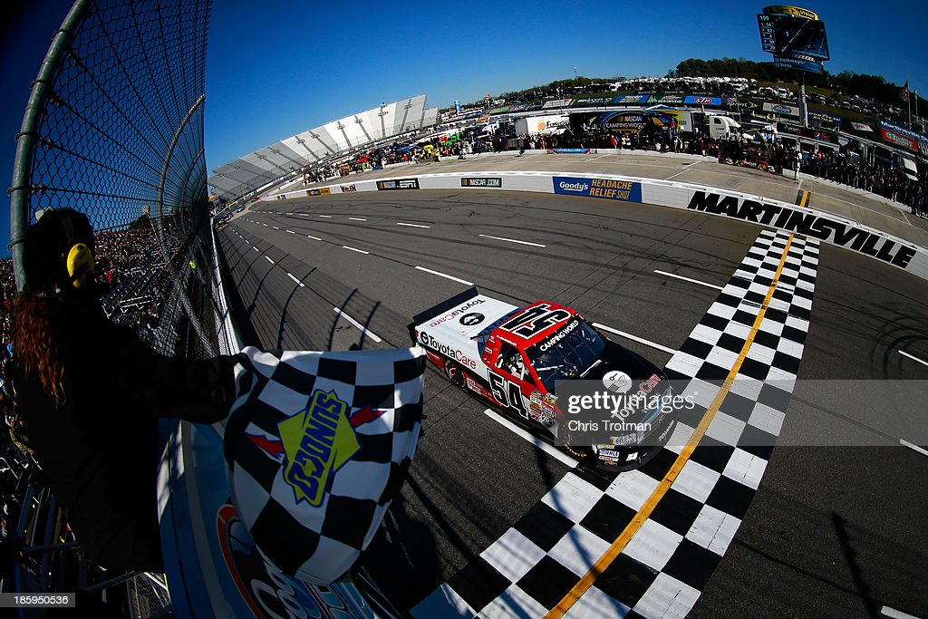 Darrell Wallace Jr., driver of the #54 ToyotaCare Toyota, crosses the finish line first to win the NASCAR Camping World Truck Series Kroger 200 at Martinsville Speedway on October 26, 2013 in Martinsville, Virginia.